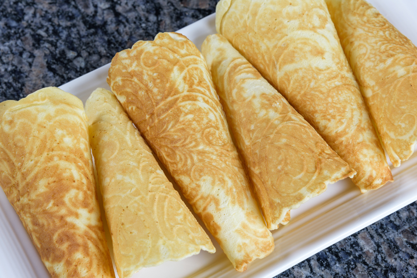 Holiday Krumkake cookies ready to eat on a white serving platter